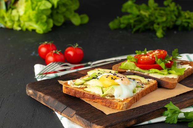 Sandwich aux œufs frits et morceaux d'avocat