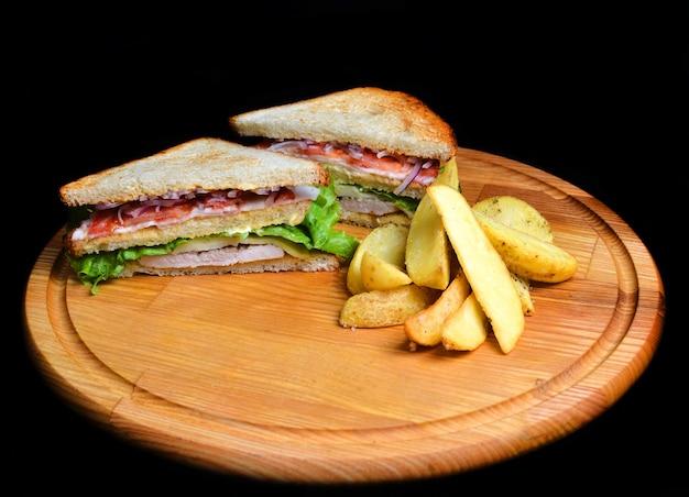 Sandwich aux pommes de terre au four sur une planche de bois isolé sur fond blanc. nourriture restaurée. fast food.