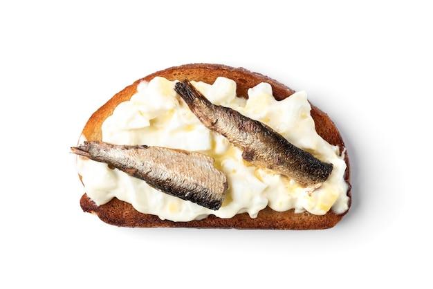Sandwich aux sprats, œufs et mayonnaise isolé sur une surface blanche.