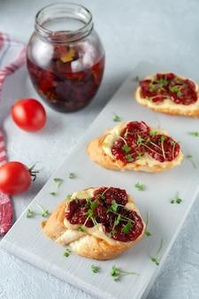 Sandwich aux tomates séchées et micro verts sur une plaque blanche