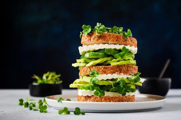 Sandwich à l'avocat, au concombre et au fromage feta décoré de microgreens et de pain multigrain sur un simple support en bois pour un petit-déjeuner sain. mise au point sélective