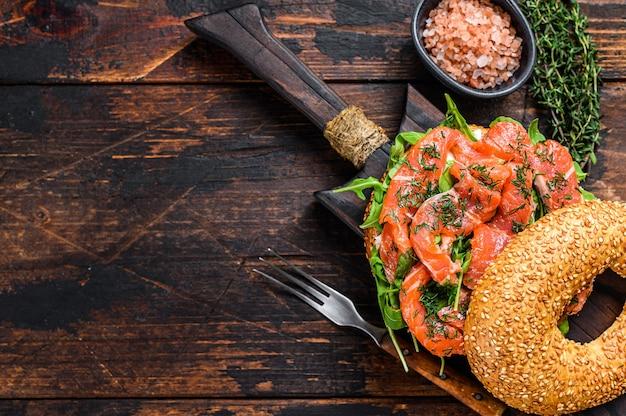 Sandwich bagels au saumon et roquette. table en bois foncé. vue de dessus.