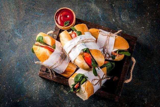 Sandwich à la baguette fraîche avec bacon, fromage, tomates et épinards