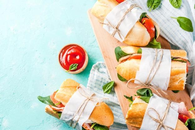 Sandwich baguette fraîche avec tomates au bacon et épinards fond bleu clair