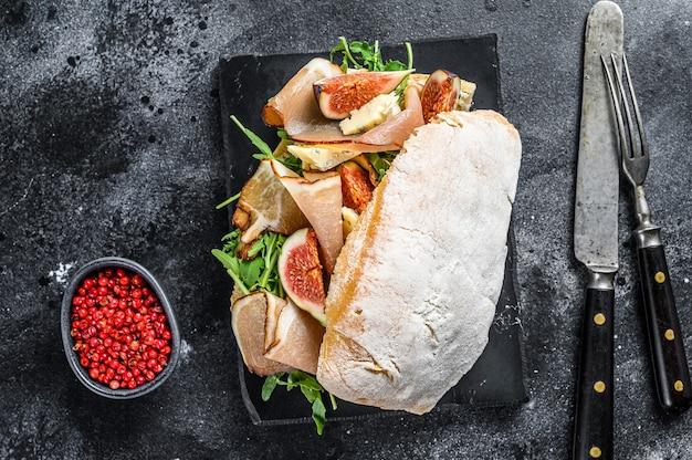 Sandwich avec baguette, jambon, figue, roquette et viande de prosciutto.