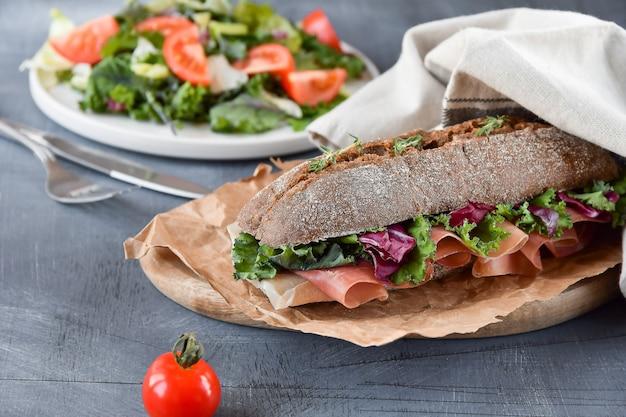 Sandwich à la baguette, jambon, laitue, kale sur fond gris
