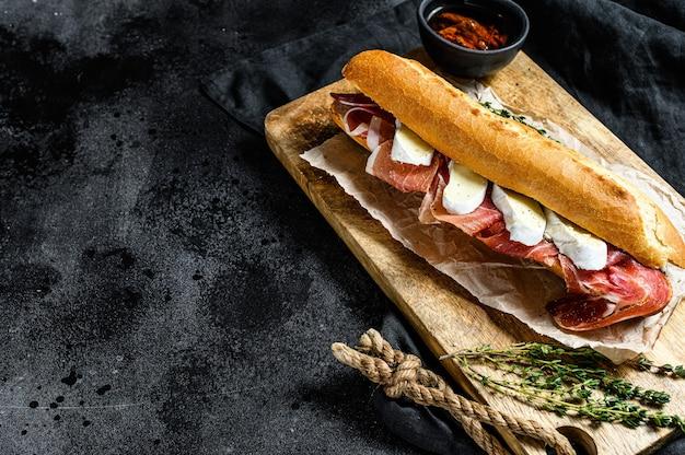 Sandwich baguette avec jambon serrano jambon, paleta iberica, fromage camembert sur la planche à découper