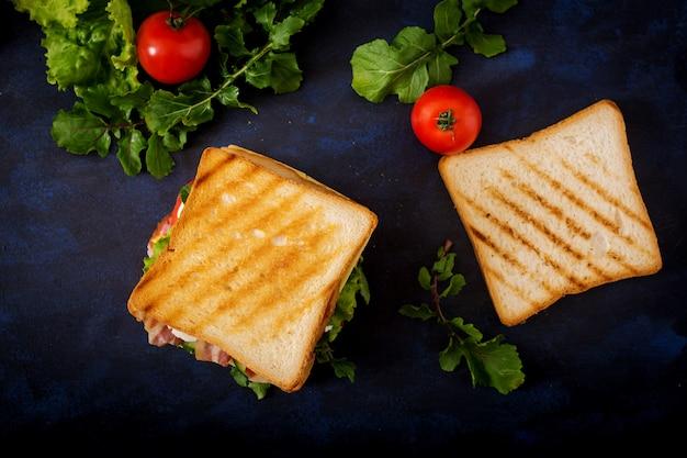 Sandwich big club avec jambon, bacon, tomate, concombre, fromage, œufs et herbes sur table sombre. vue de dessus