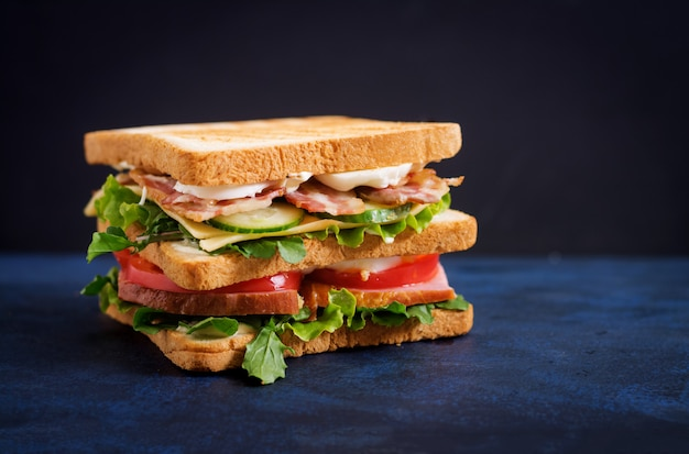 Sandwich big club avec jambon, bacon, tomate, concombre, fromage, œufs et herbes sur table sombre