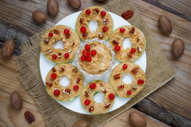 Sandwich en bonne santé. pommes vertes rondes avec beurre d'arachide et groseilles rouges et noix de pécan sur rustique, vue de dessus