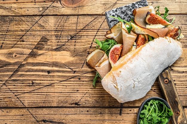 Sandwich avec ciabatta, jambon, figue, roquette et viande de prosciutto sur un couperet. fond en bois. vue de dessus.