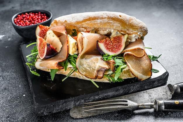 Sandwich avec ciabatta, jambon, figue, roquette et viande de prosciutto. fond noir. vue de dessus.