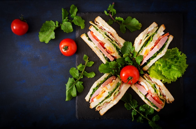Sandwich club avec jambon, bacon, tomate, concombre, fromage, œufs et herbes sur table sombre. vue de dessus