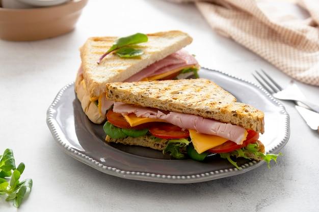 Sandwich club avec jambon de viande, laitue, fromage. sandwiches pain grillé. snack ou déjeuner.