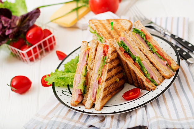 Sandwich club - panini au jambon, fromage, tomate et fines herbes.