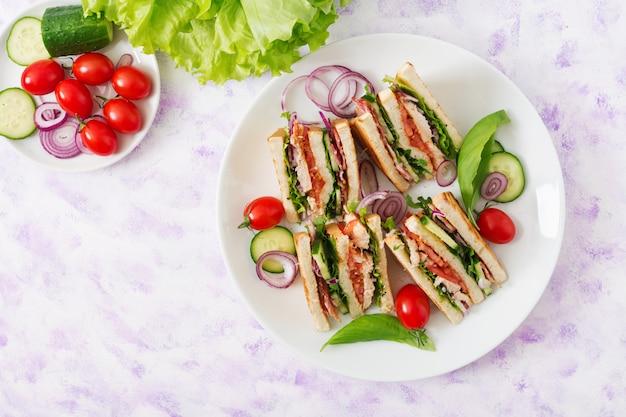 Sandwich club avec poitrine de poulet, bacon, tomate, concombre et fines herbes. vue de dessus