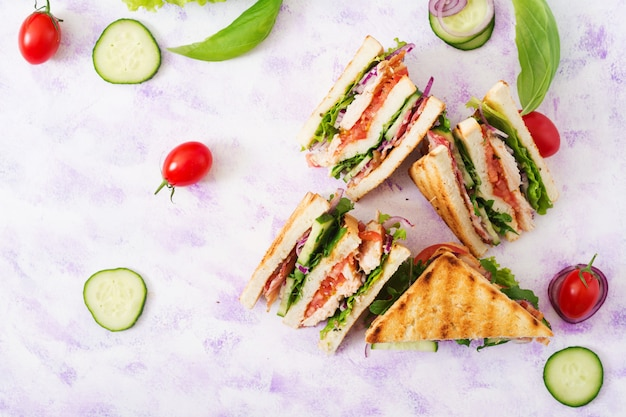 Sandwich club avec poitrine de poulet, bacon, tomate, concombre et fines herbes