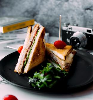 Sandwich club avec tomate sur le dessus et herbes