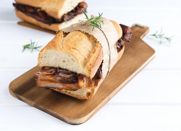 Sandwich côtelé à la sauce barbecue sur un socle en bois blanc. copiez l'espace.