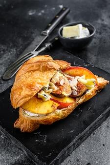 Sandwich croissant frais avec fromage brie, pêche et figues. délicieux petit déjeuner. vue de dessus.