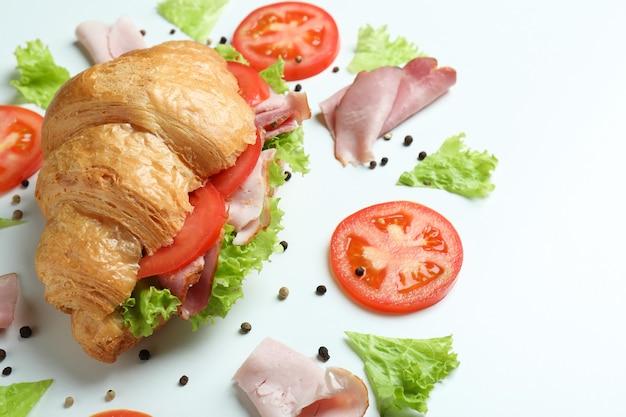Sandwich croissant et ingrédients sur blanc, gros plan