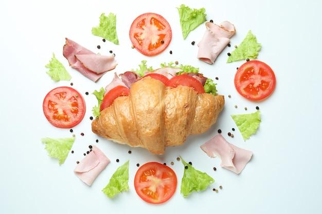 Sandwich croissant et ingrédients sur blanc, vue de dessus