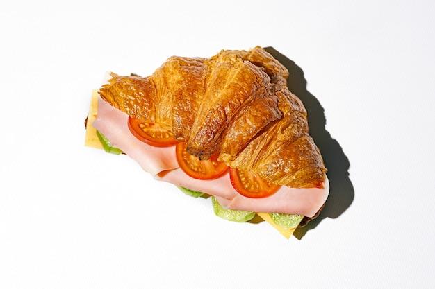Sandwich croissant avec mortadelle, fromage, roquette et œufs brouillés. lumière forte. fond blanc
