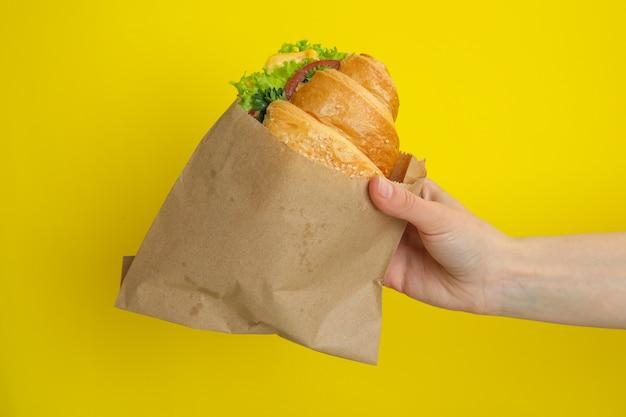 Sandwich croissant de prise de main femelle sur le jaune
