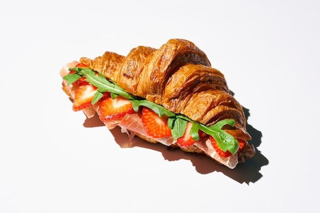 Sandwich croissant avec prosciutto, fraises, roquette et sauce balsamique. lumière forte. fond blanc