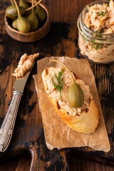 Sandwich avec délicieux pâté de poulet maison aux épices et à l'aneth dans un bocal en verre et une tranche de pain à proximité et câpres servies dans un style vintage sur une vieille planche et une table.