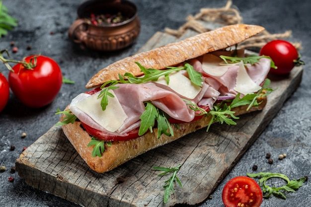 Sandwich à la dinde avec jambon, tomate, parmesan et roquette. apéritif bruschetta