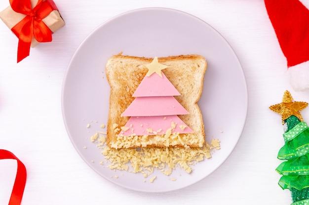 Sandwich drôle avec arbre de noël comestible à base de pain grillé, saucisse et fromage