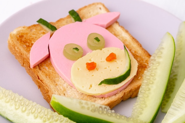 Sandwich drôle avec vache comestible à base de pain grillé, saucisse et fromage