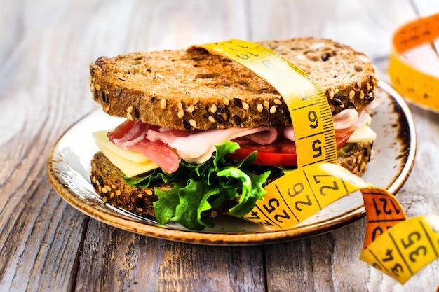 Sandwich avec du ruban de mesure sur la table en bois