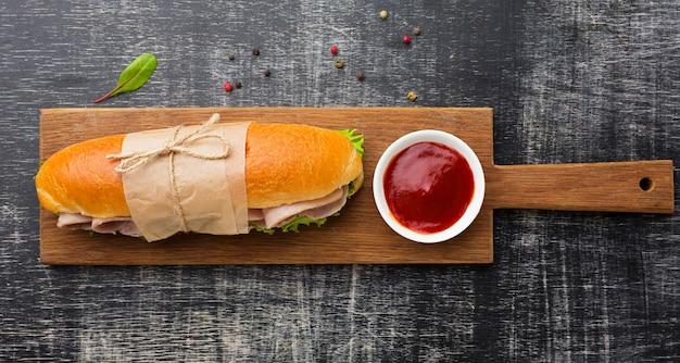 Sandwich enveloppé sur planche de bois