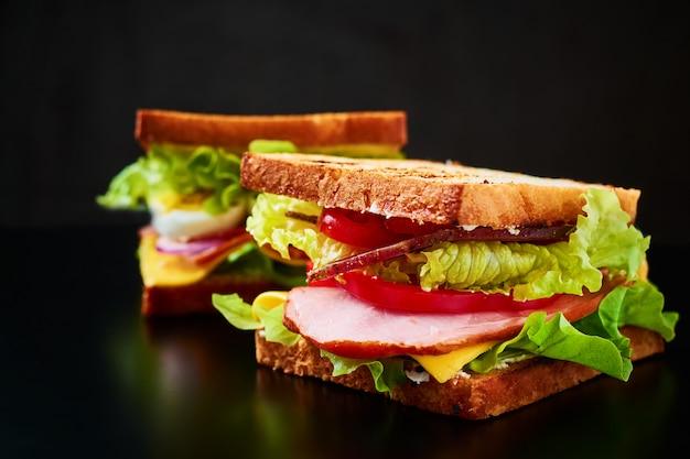 Sandwich fait maison avec de la laitue et du jambon sur fond noir, gros plan
