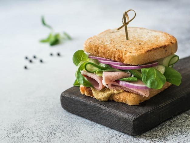 Sandwich fait maison avec viande, laitue, rondelles d'oignon rouge, concombre et moutarde de dijon sur un petit tableau noir