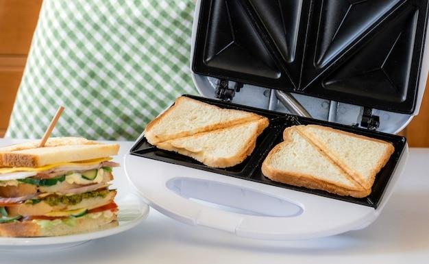 Sandwich frais au fromage, herbes, tomate, concombre et bacon sur fond de grille-pain