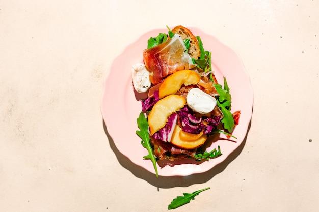 Sandwich gourmet au jambon de parme, à la mozzarella et aux pêches sur une assiette photographiée avec lumière dure, vue de dessus