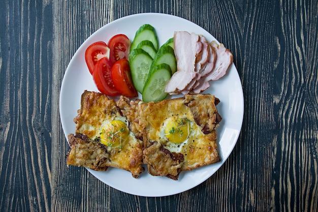 Sandwich grillé avec oeuf, légumes et bacon sur un bois foncé