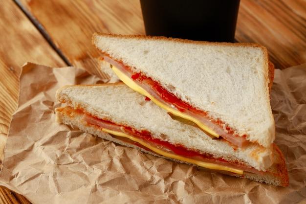 Sandwich grillé en papier kraft avec une tasse de café sur la table clsoe up