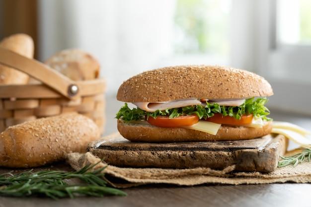 Sandwich jambon et fromage avec du pain de sésame et du pain grillé sur le panier.
