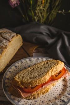 Sandwich jambon-tomate préparé avec des tranches de pain maison dans un cadre champêtre et champêtre. espace de copie, vue portrait.