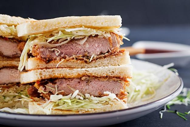 Sandwich japonais avec côtelette de porc panée, chou et sauce tonkatsu.