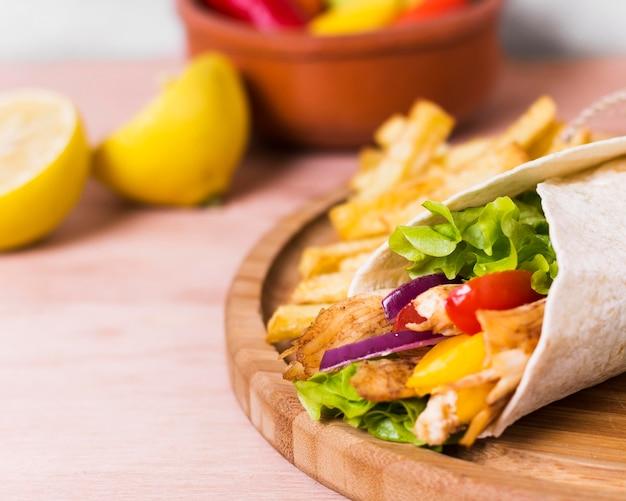 Sandwich kebab arabe enveloppé dans du papier blanc close-up