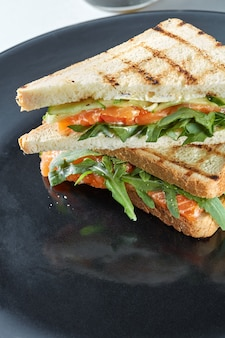 Sandwich macro au saumon sur une plaque noire