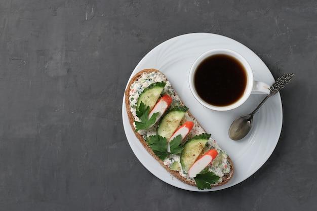 Sandwich maison avec bâtonnets de crabe, concombre, fromage à la crème et une tasse de café sur une surface sombre