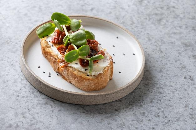 Un sandwich avec des micropousses de radis frais et des tomates séchées au soleil sur fond gris. fermer.