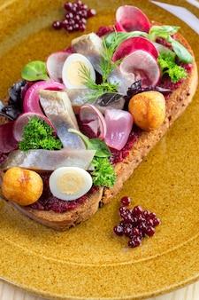 Sandwich avec des morceaux de hareng mariné