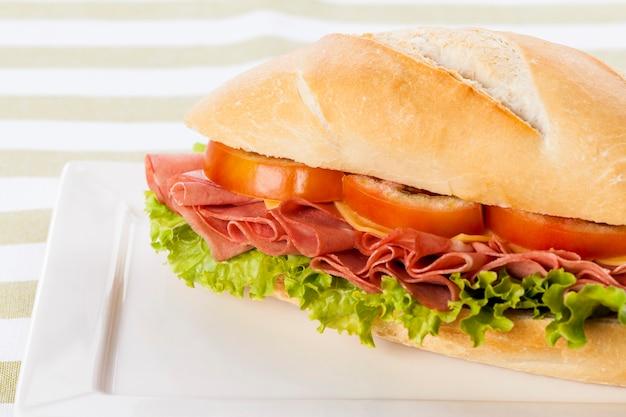 Sandwich à la mortadelle, sur fond blanc et vert